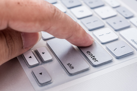pressing: hand pressing enter button on computer Stock Photo