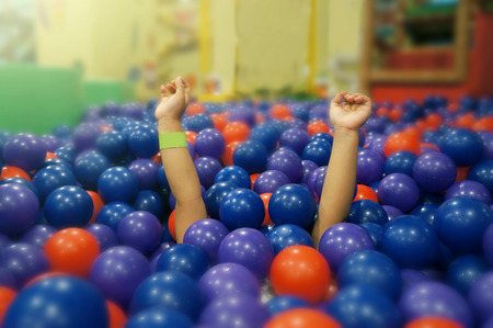 The little girl is under a plastic ball in Ball pit. She lifted her arms and made fun sounds.