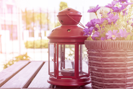 Red lamp set near the flowerpot on the table.