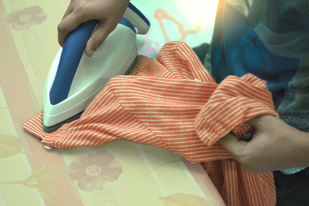 Young woman holds the iron in her hand, she is ironing the baby. Stock Photo