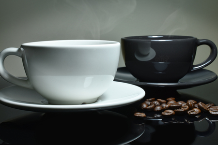 top animated: White and black Coffee cup, coffee beans on black table,  Focus white cup. Stock Photo