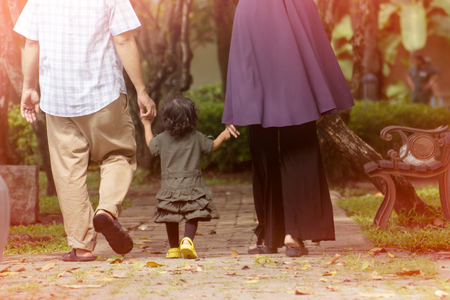 Muslim families, husbands, wives and children. They were walking holding hands in a park in Thailand.