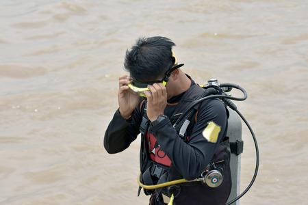 Asian guy he is in a dive series. And prepare before going down in a river.