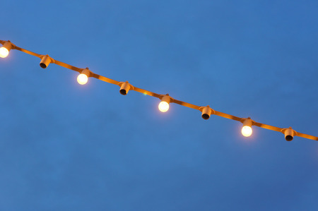 Halogen light bulbs hanging from the roof to the tree. It was introduced to various Festival decoration. Imagens