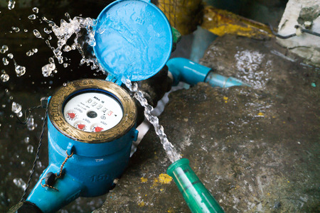 Close up water meter blue color in thailand. And a hose with flowing water.