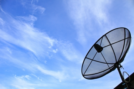 A satellite dish on the roof of the house with the blue sky  photo