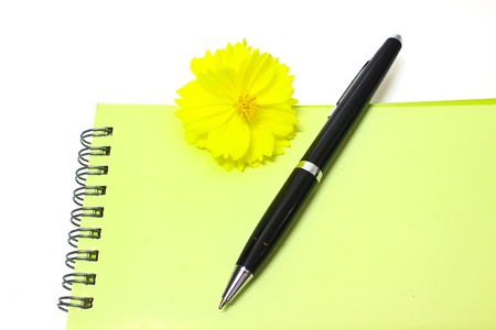 Pen resting on notebook and Yellow flower isolated on the white background photo