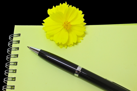 Pen resting on notebook and Yellow flower isolated on the black background photo
