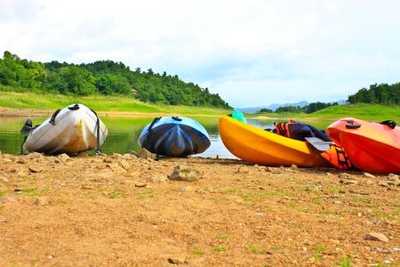 Kayaks, canoe  on the edge of the water in Lake Dam Kaeng Krachan, Thailand photo