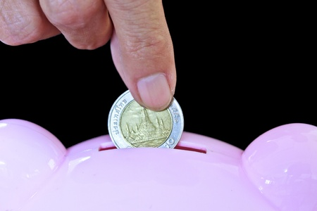 Hand inserting coin into piggy bank photo