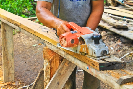 Hand carpenter using wood planer, construction worker