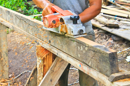 wood planer: Hand carpenter using wood planer, construction worker