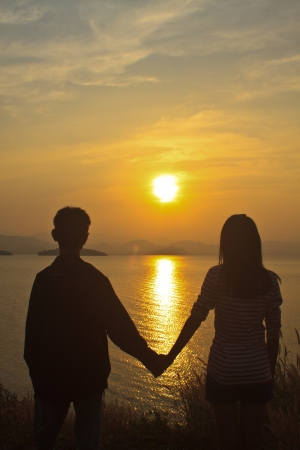 couple in love back light silhouette at lake, sunset background photo