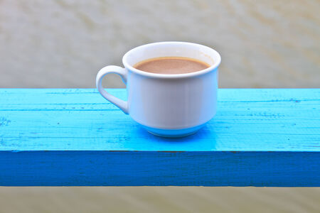hot coffee in white cup on wooden, During leisure time on river background