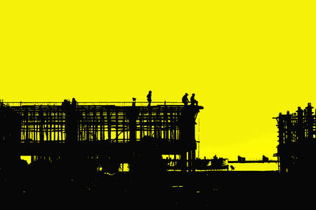 Construction worker working on a construction site on silhouettes photo
