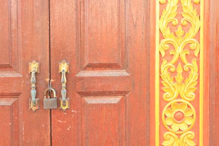Cerradura con cerrojo de la puerta roja que se encuentra en un templo en Tailandia Foto de archivo - 26159524