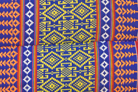 gaudy: Thai Esan traditional pillows have a specific shape like cube and contain the pure cotton inside. The pillow surface has a specific weaving pattern and gaudy color. Handcraft art. Stock Photo