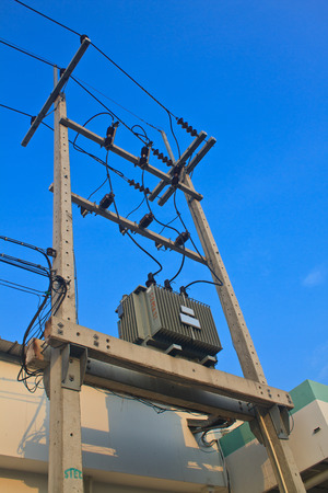 tangling: Transformers of an electrical post with power-lines against bright blue sky