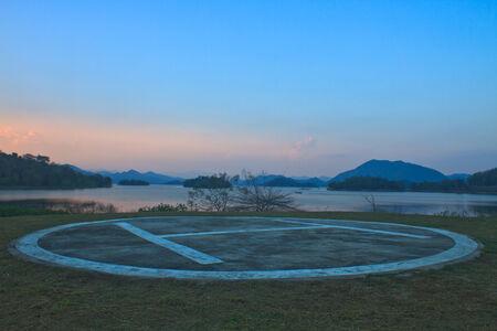 helipad: Helipad area for helicopter parking near lake on sunset Stock Photo