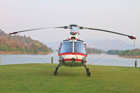 landing strip: helicopter standing on landing strip in airfield near lake in morning Stock Photo