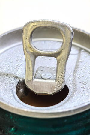 inhibited: Closeup shot from the pull ring on a beverage can, opened aluminum can with water drop