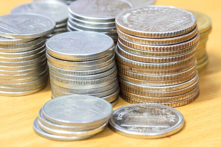 stack of coins isolated on wood table background photo