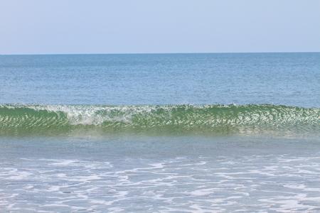 Soft wave of the sea on the sandy beach photo