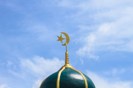 Gold islamic religious symbol on top of a mosque dome against blue sky background photo