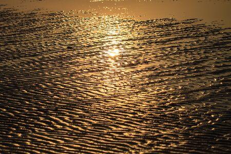 Beach sand waves warm texture pattern background with sunrise shadow photo