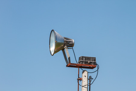 Speaker megaphone white on pole with blue sky in background