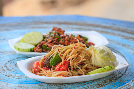 Thai delicious raw papaya salad with Thai cuisine spicy pork salad