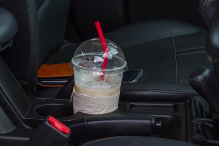 Cup of coffee with wallet  and smartphone on car console Фото со стока