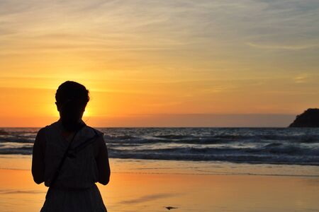 happieness: silhouette of a woman on a beach at sunset  Stock Photo