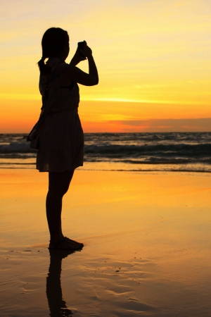 Silhouette of woman on the beach Stock Photo