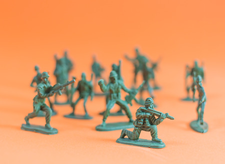 Closeup of action mini toy soldier on orange background Stock Photo