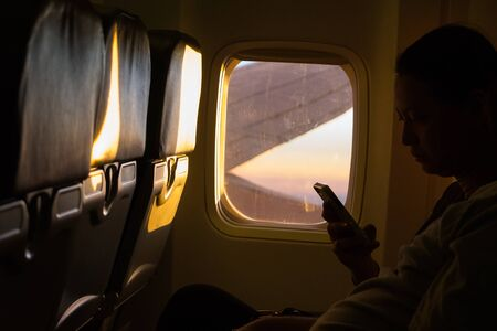 undefined: CHIANG MAI ,THAILAND - APRIL 27 ,2015 : Undefined traveler holding smart phone in the airplanes while flying, on April 27, 2015 in Chiangmai,Thailand.