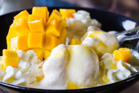 Vanilla Ice Cream Met Verse Mango's op zwarte plaat Stockfoto