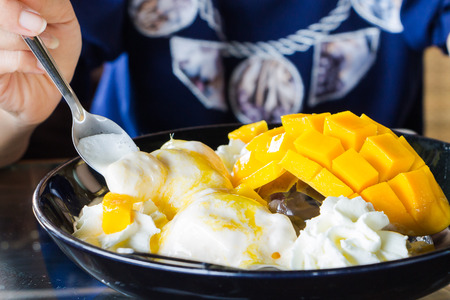 summer pudding: Vanilla Ice Cream With Fresh Mangoes on Black plate