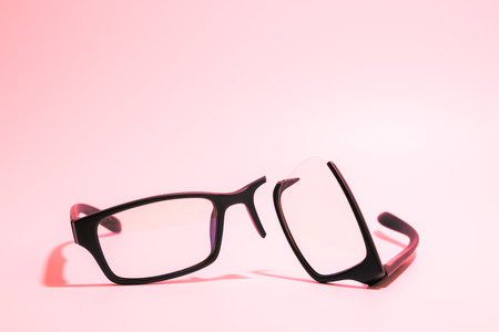 myopic: Closeup of Broken plastic Eyeglasses on colored background Stock Photo