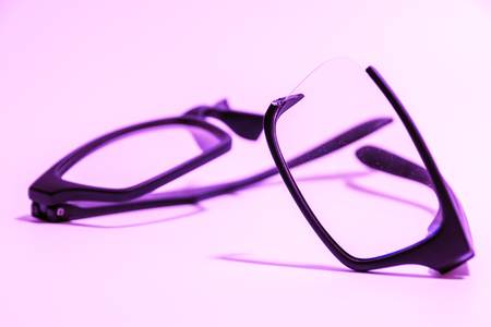 rimmed: Closeup of Broken plastic Eyeglasses on colored background Stock Photo