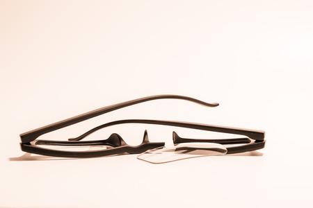 astigmatism: Closeup of Broken plastic Eyeglasses on colored background Stock Photo