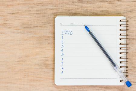 metas: Objetivos para el 2016 - lista de verificaci�n en la libreta con la pluma en el fondo de madera