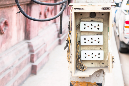 power pole: Wall plug on power pole on the side of the road. Stock Photo