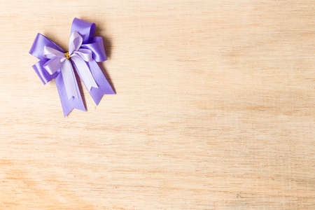 purple ribbon: Purple ribbon bow  on wooden background