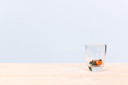 medicaments: Pill in glass on wooden floor and concrete background