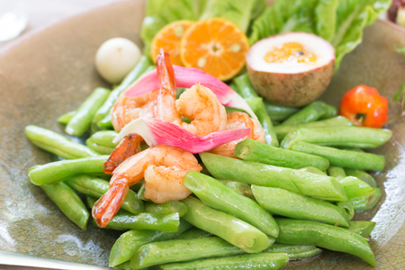Fried long beans with prawns  with  slices of orange and passion fruit Stock Photo