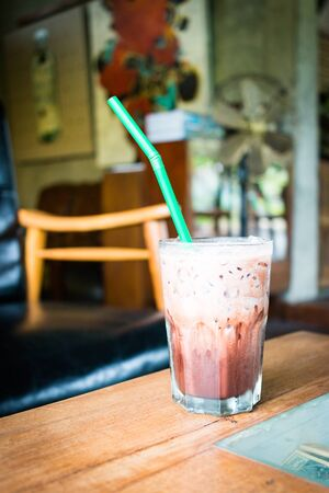 Iced chocolate on wooden table in coffee shop  background
