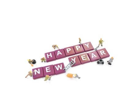 Miniature worker team building word happy new year on white background Stock Photo
