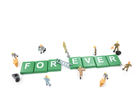 Miniature worker team building word forever on white background