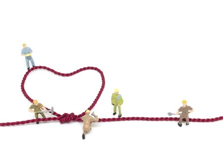 Miniature worker team building Heart Shaped with rope on white background Stock Photo